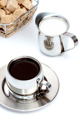 Cup of black coffee with brown sugar and milk
