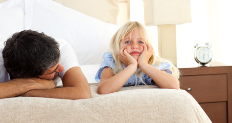 Little girl lying on bed with her father