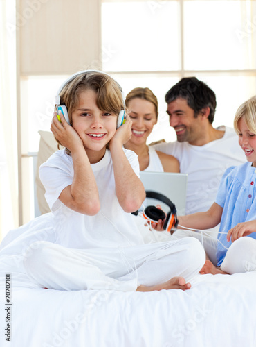 Happy little boy listening music sitting on bed