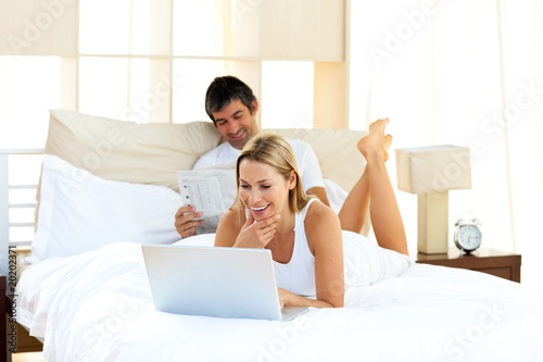 Positive woman using a laptop lying on bed