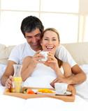 Fototapety Loving couple having breakfast lying in the bed
