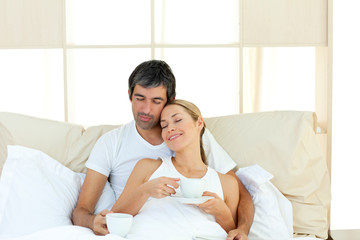 Positive couple drinking coffee lying in the bed