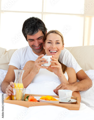 Loving couple having breakfast lying in the bed