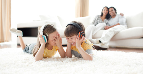 Laughing children listening music with headphones