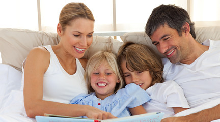 Joyful family reading a book on bed