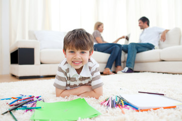 Smiling child drawing lying on the floor