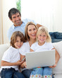 Cute children with their parents using a laptop