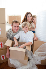 Happy family packing boxes