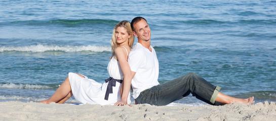 Portrait of couple sitting on sand