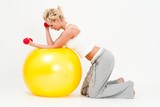 woman exercising with dumbbells on a big fitness ball
