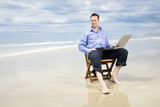 business man sitting on a chair on the beach with laptop - Fine Art prints