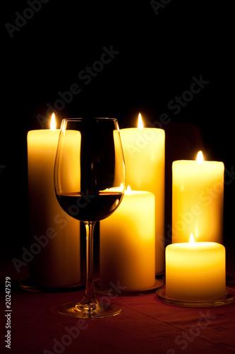 Rotweinglas vor brennenden Kerzen