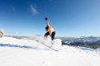 Snowboarder jumps up at mountain top