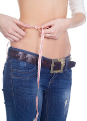girl measuring her waist with a measuring tape