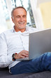 Mature man with laptop smiling