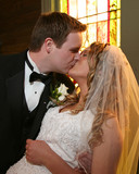 Bride and groom kissing at the church altar poster