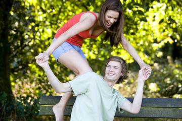 A young couple having fun on a park bench