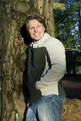 happy smiling outdoor man leaning on tree