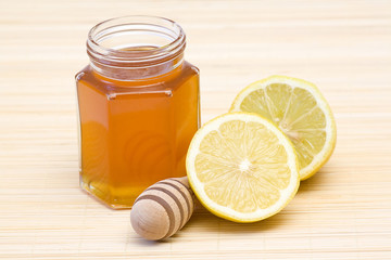 jar of honey, lemon and wooden drizzler