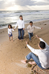 Happy African-American family running to father on beach