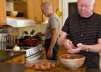 Mature married gay couple cooking dinner