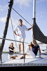 Teenage girl and parents on sailboat at dock