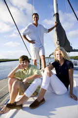 Father and teenage children on sailboat at dock
