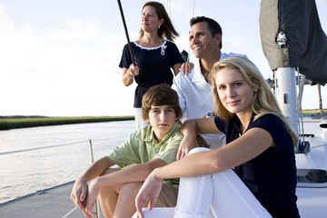 Family with teenage children sitting on boat at dock