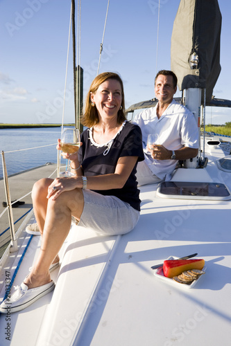 Mid-adult couple sitting on deck of boat enjoying drink