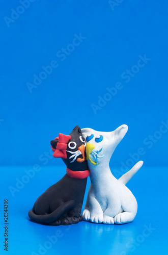Two sweet clay black and white cats in love with copyspace