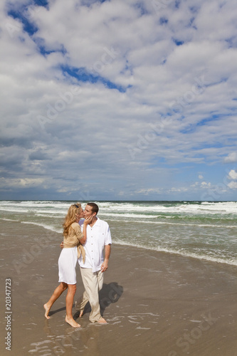 Man and Woman Couple Walking and Kissing On A Beach