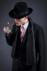 business man sets fire to the cigar from the dollar