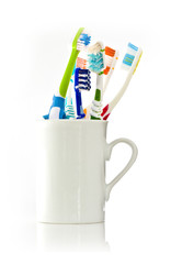 Toothbushes in a white mug