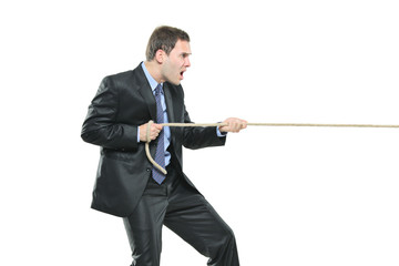 A young businessman pulling a rope isolated on white