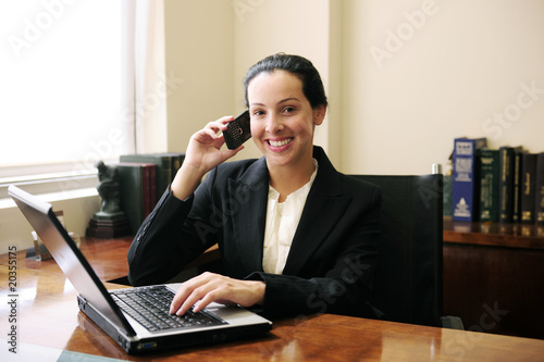 female lawyer at office talking on phone and using laptop