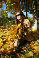 The woman squats with an armful of maple leaves