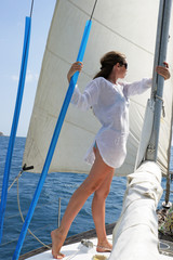 The girl stand on the yacht undertaken a mast
