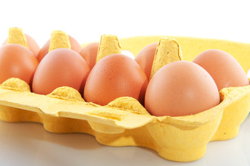 Brown eggs in yellow carton