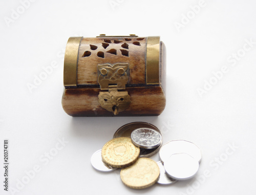Coins against the wooden varnished ancient chest