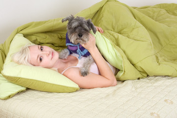 young woman in bed playing with schnauzer dog