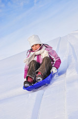 Girl slides down a hill on a sledge on a background of blue sky