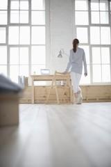 Woman walks across loft apartment