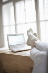 Feet up in loft apartment with laptop