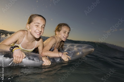 Twin sisters wave surfing on airbed