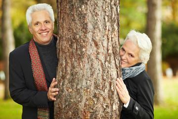Zwei Senioren hinter Baumstamm