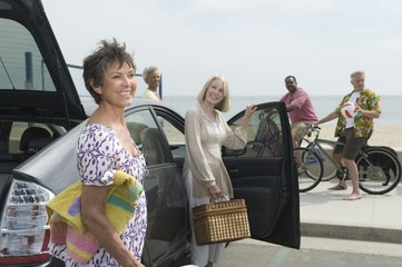 Senior women unpack car observed by men on bicycles