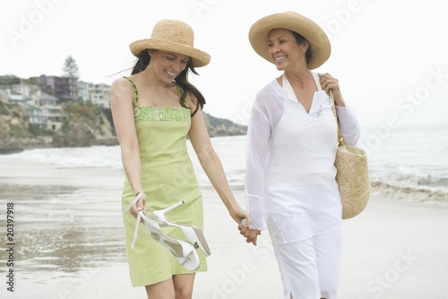 Mother and daughter walk along beach holding hands