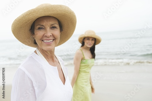 Mother and daughter in sunhats on beach