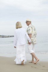 Senior couple walk holding hands on beach