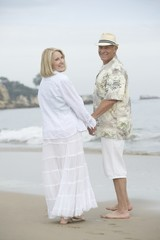 Senior couple stand holding hands on beach
